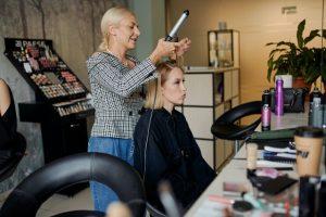 фризьорка прави прическа на жена